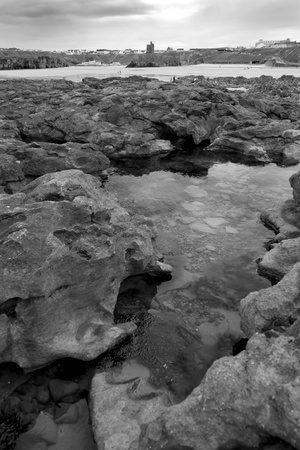 strange rock formations on the beach in ballybunion county kerry ireland with town and castle in background in black and white photo
