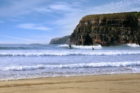 beautiful clean atlantic ocean with surfers catching the waves with cliffs in background on Irelands coast photo