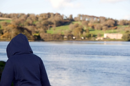 young hoodie wearing teenager exploring by a river in county waterford ireland with large mansion in background photo