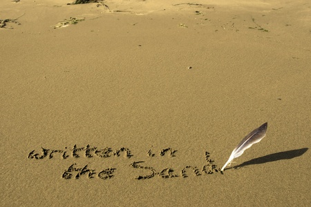 written in the sand inscribed on a sandy beach with a feather quill photo