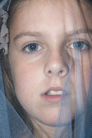 a beautiful young girl staring out from beneath a blue veil photo