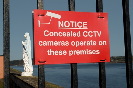 concealed cctv cameras in operation sign with virgin Mary statue in the background photo