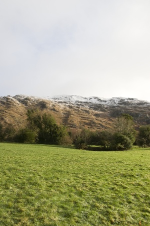 rocky mountain and fields countryside snow scene in irish speaking area of county Kerry Ireland with copyspace photo