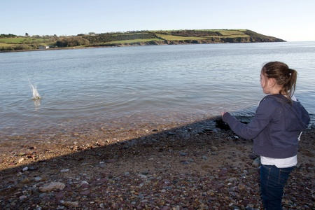 youghal: young girl throwing stones from the shore into the sea