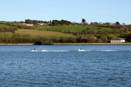pair of jetskiers racing up the blackwater river in ireland photo