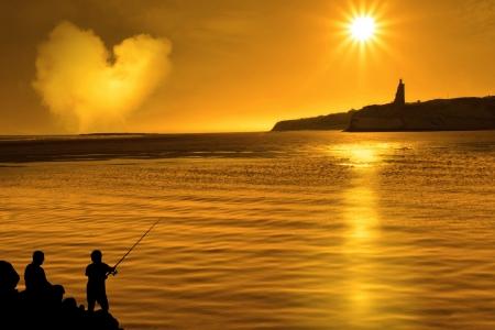 hombre pescando: una silueta de una pesca de padre e hijo de las rocas en Irlanda