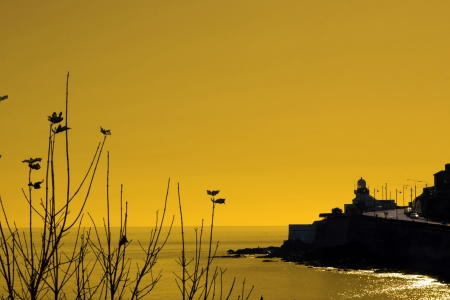 youghal: view of youghal lighthouse looking out on the atlantic ocean on a sunset eve