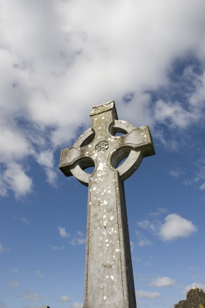 old celtic cross in an irish graveyard with blue cloudy sky photo