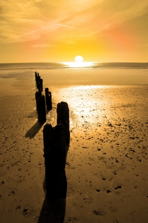 youghal: wave breakers at sunset on a golden beach in youghal county cork ireland