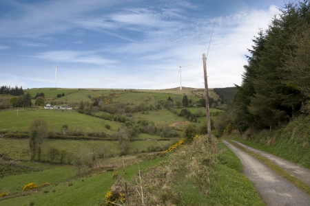 country lane in the irish countryside leading to a hill with windmills photo