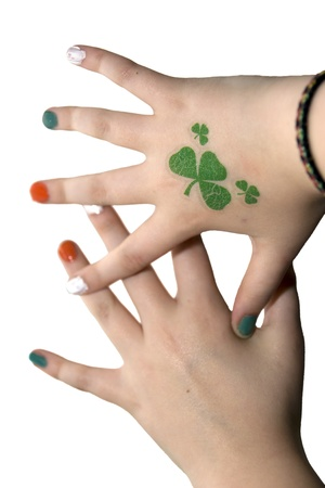bracelet tattoo: young girls hands with a shamrock tattoo and painted finger nails Stock Photo