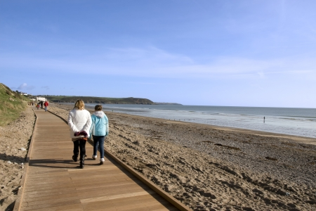 youghal: mother and daughter strolling along the beach boardwalk in Youghal county Cork Ireland Stock Photo