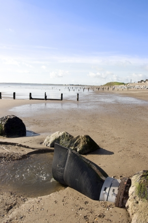 youghal: sewerage pipe among the beach breakers in Youghal county Cork Ireland on a summers evening Stock Photo