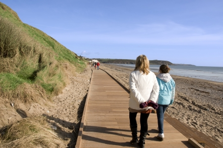 mother and daughter strolling along the beach boardwalk in Youghal county Cork Ireland Stock Photo - 16714836