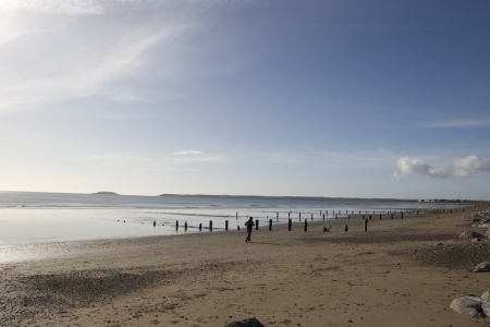 youghal: sunshine over the beach breakers in Youghal county Cork Ireland on a summers day with jogger Stock Photo