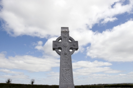 an old celtic cross in an irish graveyard with blue cloudy sky and countryside