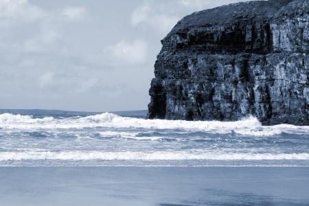headland: Ballybunion beach and cliffs on the Atlantic coast in Ireland with waves crashing on the cliffs Stock Photo