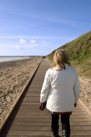 youghal: woman strolling along the beach boardwalk in Youghal county Cork Ireland