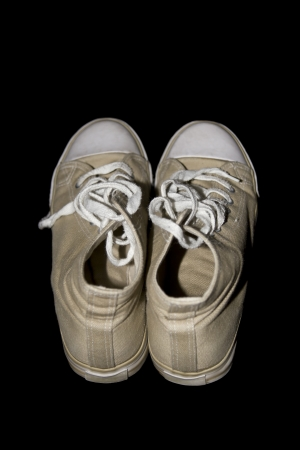 beige classic youth canvas shoes on a black background with a clipping path photo