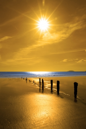 youghal: golden sunshine over the beach breakers and blue Atlantic sea in Youghal county Cork Ireland on a summers day