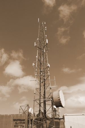 a steel telecommunication tower with a cloudy sky background in sepia photo