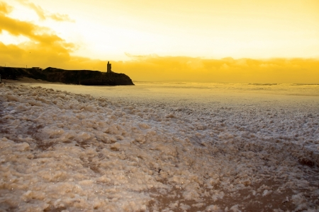 sweeping waves of foam crashing against Ballybunion beach on a dark sunset evening during a storm of the west coast of ireland photo