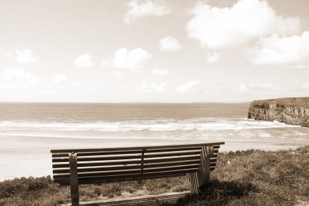 ballybunion: Beautiful view over the Ballybunion beach and cliffs in Ireland from a wooden bench in sepia