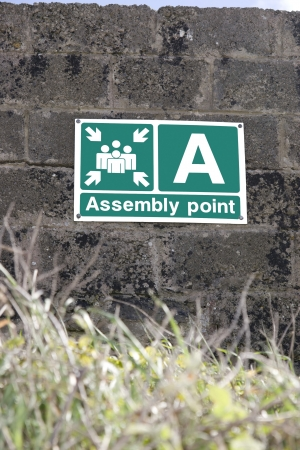 an assembly point sign on a block wall in Ireland