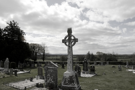 old ancient Celtic graveyard with marked gravestones and flowers in Ireland photo