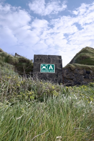 an assembly point sign on a block wall at a beach in Ireland Banco de Imagens