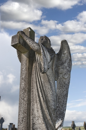 monastic site: Angel statue embracing a cross and celtic graveyard  in Ardmore county Waterford, Ireland with added grain