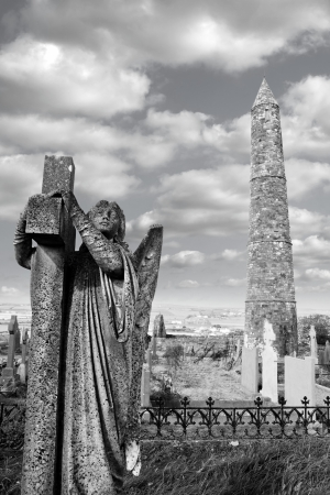 Angel statue before an Ancient round tower and celtic graveyard with cathedral in Ardmore county Waterford, Ireland in black and white and added grain photo