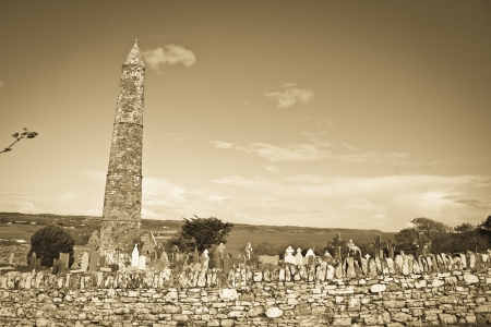 monastic sites: sepia Ancient round tower and celtic graveyard with cathedral in Ardmore county Waterford, Ireland  Stock Photo