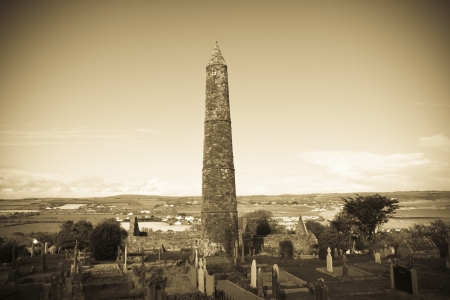 monastic sites: Ancient round tower and celtic graveyard with cathedral in Ardmore county Waterford, Ireland  Stock Photo