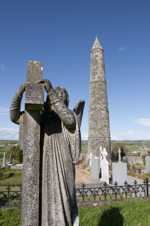 Angel statue before an Ancient round tower and celtic graveyard with cathedral in Ardmore county Waterford, Ireland photo