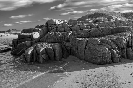 old natural rock formation on a beach in county Donegal, Ireland in black and white photo