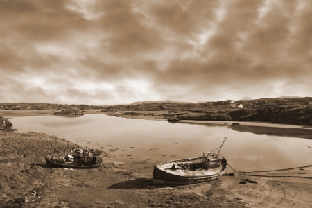 beached: two old fishing boats beached on a coastal beach in county Donegal, Ireland in sepia