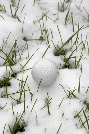 a lone single golf ball in the snow covered grass in Ireland at winter photo