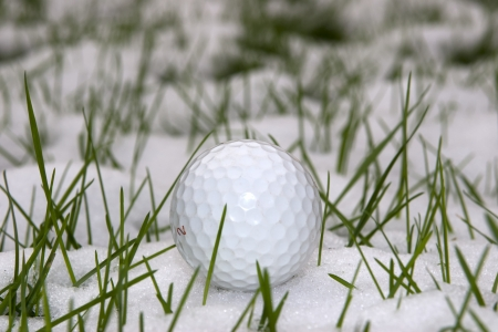 a lone single golf ball in the snow covered grass in Ireland at winter