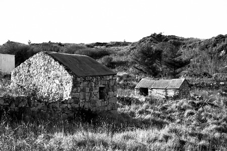old rustic stone buildings in county Donegal Ireland in black and white photo