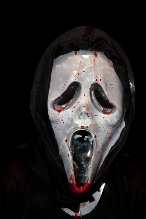 a hooded person in a halloween mask splattered in blood photo