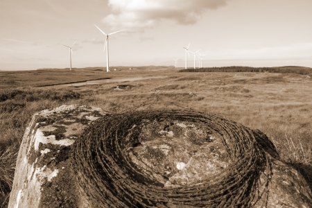 a roll of barbed wire on a rock with wind turbines in the background in Ireland sepia toned photo