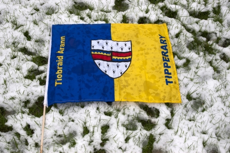 the Tipperary flag against a snow covered green grass background photo