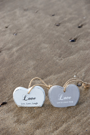 quicksand: two inscribed wooden love hearts sinking in the quicksand on a wild Atlantic way Irish beach in summer