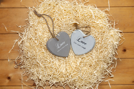 two wooden love hearts in a love nest made of straw on floor boards photo
