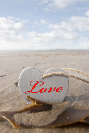 inscribed: inscribed wooden love heart in the sand on a wild Atlantic way Irish beach in summer with copy space
