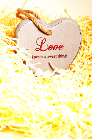 single wooden love heart in a hot love nest made of straw photo