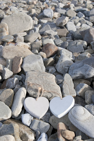two wooden love hearts on the rocks of a beach photo