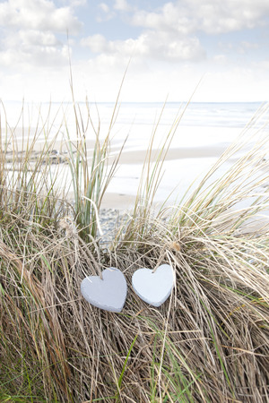 two blue wooden love heart in dunes on an Irish beach in summer photo