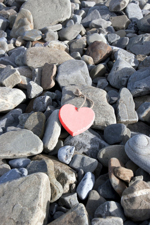 red pebble: single red hot wooden love heart on a pebble beach in Ireland